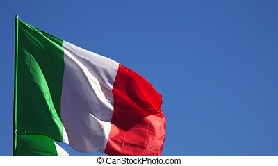 Flag Of Italy on the background of the sky and flying clouds.