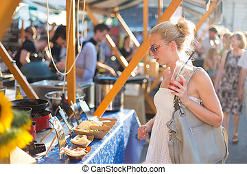 Woman buying meal at street food festival.