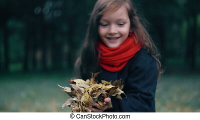 closeup of a beautiful cute little girl collects yellow...