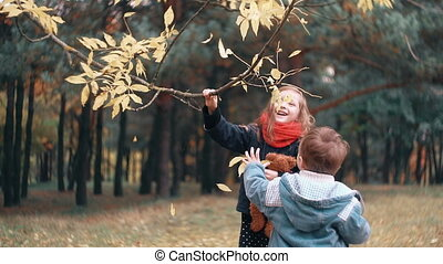 funny little girl shakes branch of tree and yellow autumn leaves fall from it her younger brother tries to make how she