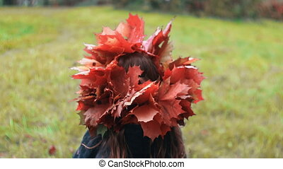 back view cute little girl in a wreath crown of autumn maple leaves walks in the park slow motion