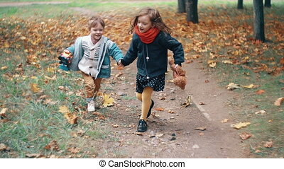 cute brother and sister little boy and girl running holding hands, with their toys through autumn alley in park slow mo