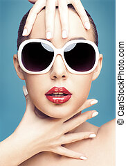 young woman wearing sunglasses - close up studio portrait of...