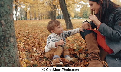 little boy looks at smartclock on mother's hand in autumn park