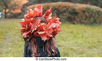 Girl goes back and then turns around and looks at the camera. cute little girl in a wreath crown of autumn maple leaves.