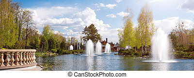 Ornamental gardens with lake, blooming bushes and fountains. Banner for website