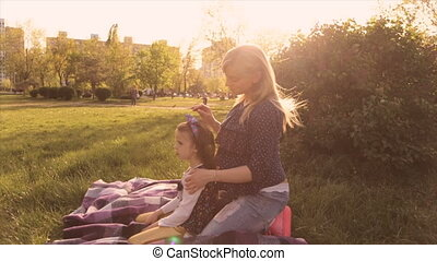 Happy family, mom and daughter playing in the meadow - My...