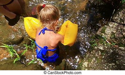 Small Blond Girl in Armbands Bathes in Mountain River -...