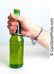 Glass of beer with handcuffs as symbol for alcohol abuse