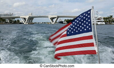 American flag waves on a boat navigating in a canal in Fort...
