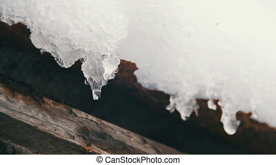 Spring Snow Melting on the Roof Old House. Close-up. Icicles...