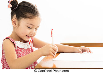 happy little girl writing at desk in classroom