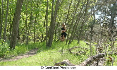 A girl is running around in the woods