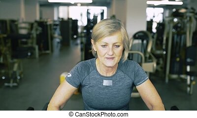 Fit senior woman in gym on treadmills doing cardio work out.