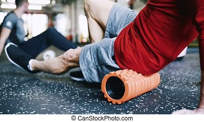 Unrecognizable man in gym exercising with foam roller. -...