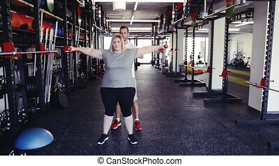 Overweight woman in modern gym working out with dumbbells. -...