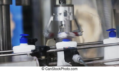 automatic robot twists the caps on a conveyor belt