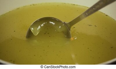 Slow motion. Scoop up broth from a saucepan with a ladle -...