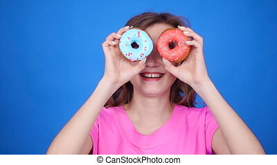 Beauty woman taking colorful donuts. Funny joyful girl with...