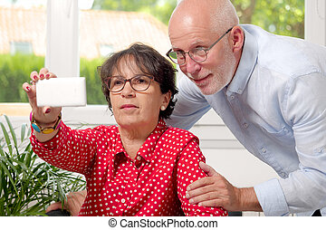 Cheerful senior couple taking selfie at home - a cheerful...