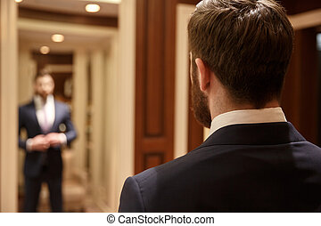 Man looking in mirror wearing suit - Close up shot of back...
