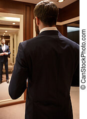 Vertical image of bearded man correcting his suit against...