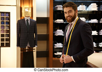 Smiling man standing in wardrobe with measure tape -...
