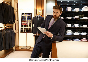 Serious man in wardrobe with tablet - Portrait of serious...