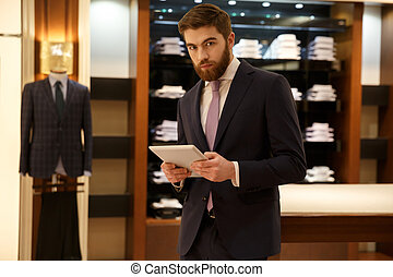 Businessman with tablet in wardrobe - Serious bearded...