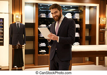 Cute man in suit using tablet - Cheerful bearded man using...