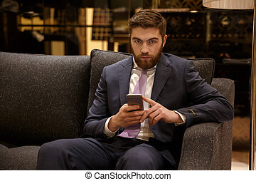 Bearded businessman with phone looking seriously in camera -...