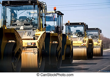 Group of yellow asphalt compactors on road - Several yellow...