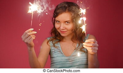 Young attractive celebrating woman holding sparkles and dancing