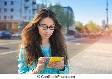 Beautiful young woman in glasses with a smartphone writing -...