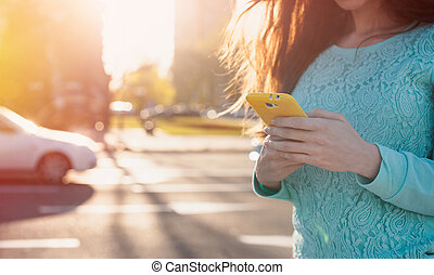 young woman with smartphone writes - young woman with a...