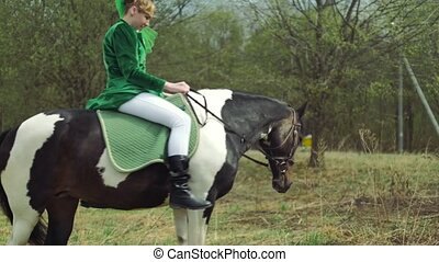 A woman in a green suit is riding a horse 4k - A woman in a...