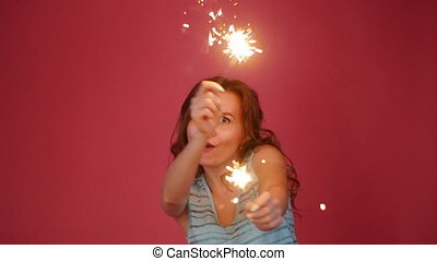 Young attractive celebrating woman holding sparkles and...