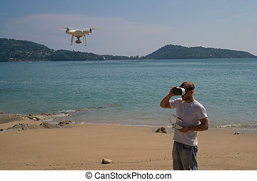 Man with drone camera and virtual reality glasses taking...