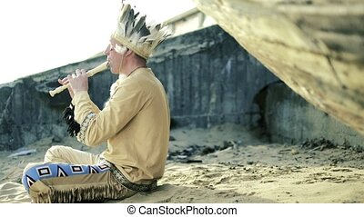 An Indian in a national costume plays a flute near a boat on...