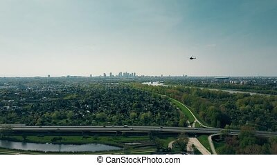 Aerial shot of a helicopter flying above highway against...