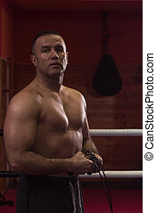 portrait of muscular professional kickboxer who standing in...