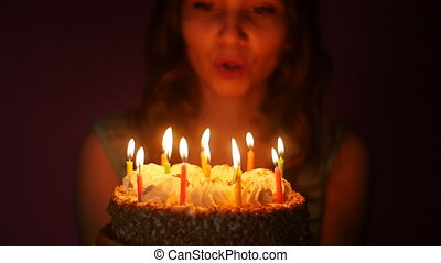 Young woman blowing out candles on a birthday cake in slow...