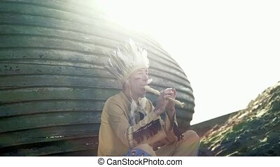 An man in costume plays a flute near a boat on the river...