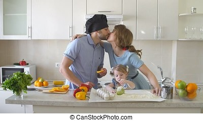 Happy Young Family Spending Time in The Kitchen. - Happy...