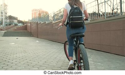Beautiful woman rides a bicycle near a tall building 4k -...