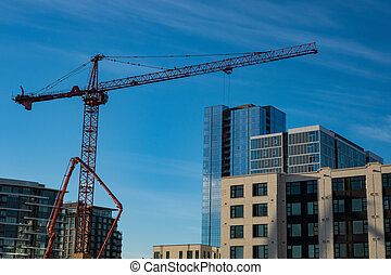 Construction crane and new buildings against blue sky -...