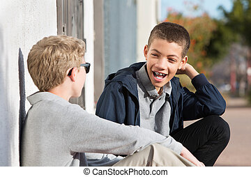 Laughing teen with braces beside friend