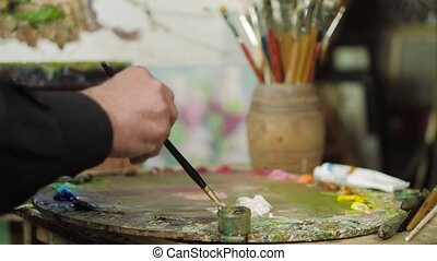 An elderly artist writes a picture in his studio 4k