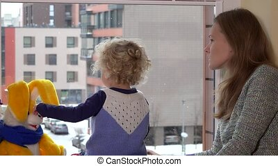 mother with cute daughter enjoy snow falling through window and wave hands