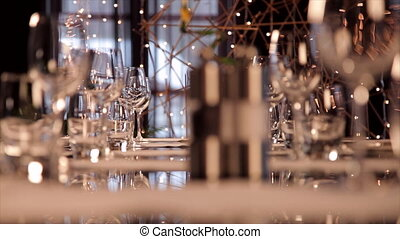 Restaurant table set with glassware. Bokeh lights on the...